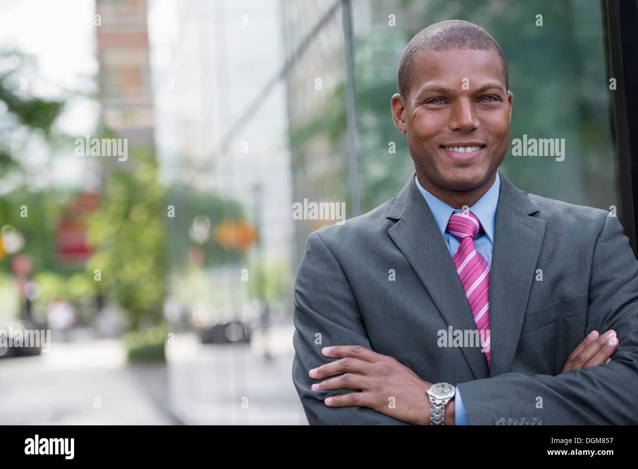Un hombre joven en un traje de negocios con una camisa azul y corbata roja. En una calle de la ciudad. Sonriendo Foto de stock