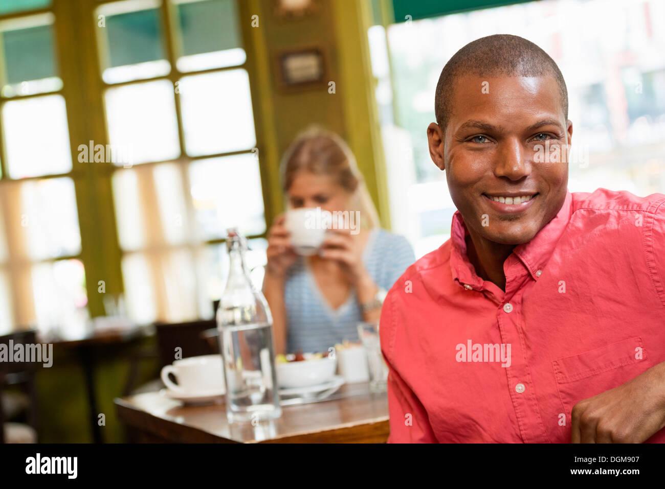 Una pareja en una cafetería de la ciudad. Sentado en una mesa. Una mujer sosteniendo una taza de café. Foto de stock