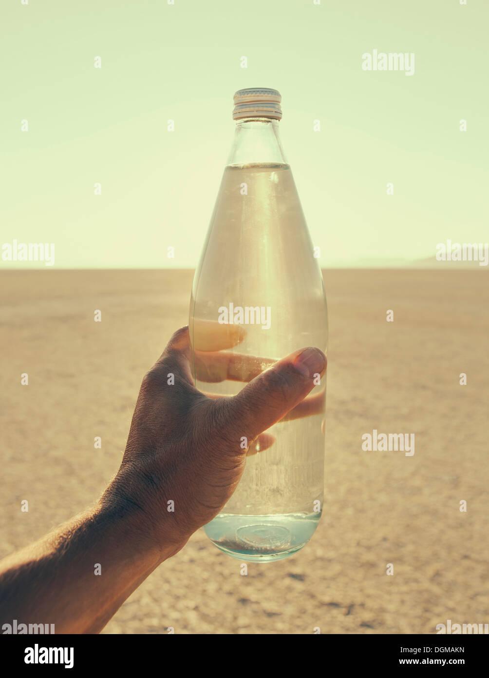 El paisaje del Desierto Black Rock de Nevada. Una mano de hombre sosteniendo una botella de agua. Filtra agua mineral. Imagen De Stock