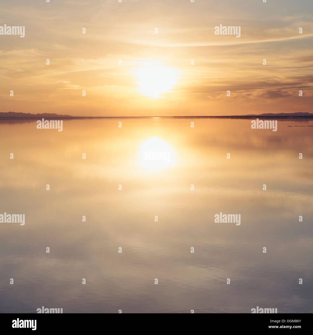 Aguas poco profundas sobre la superficie en las salinas de Bonneville, en la puesta de sol. Foto de stock