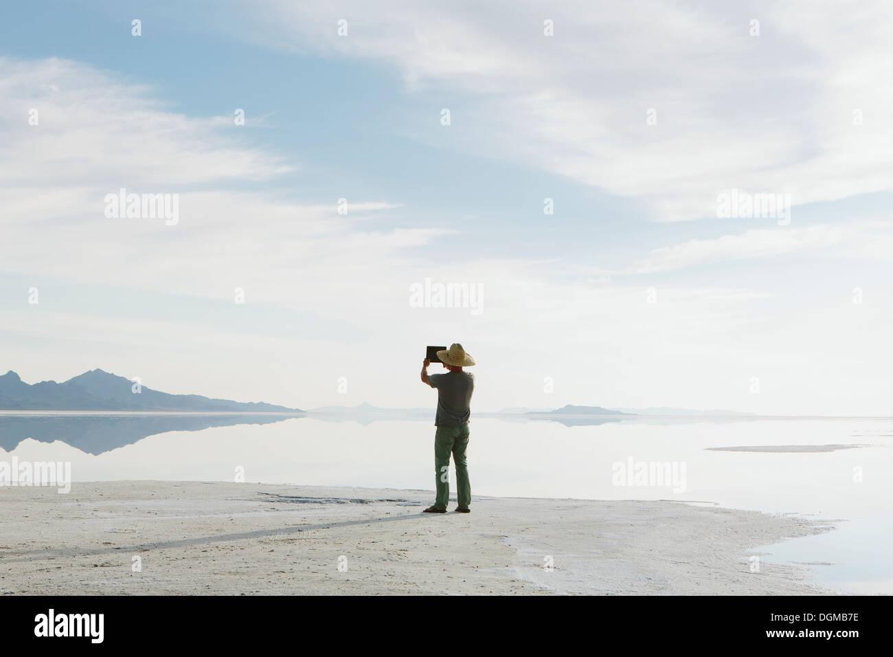 Un hombre de pie en el borde de las salinas de Bonneville inundado al atardecer, tomar una fotografía con un dispositivo tablet. Imagen De Stock
