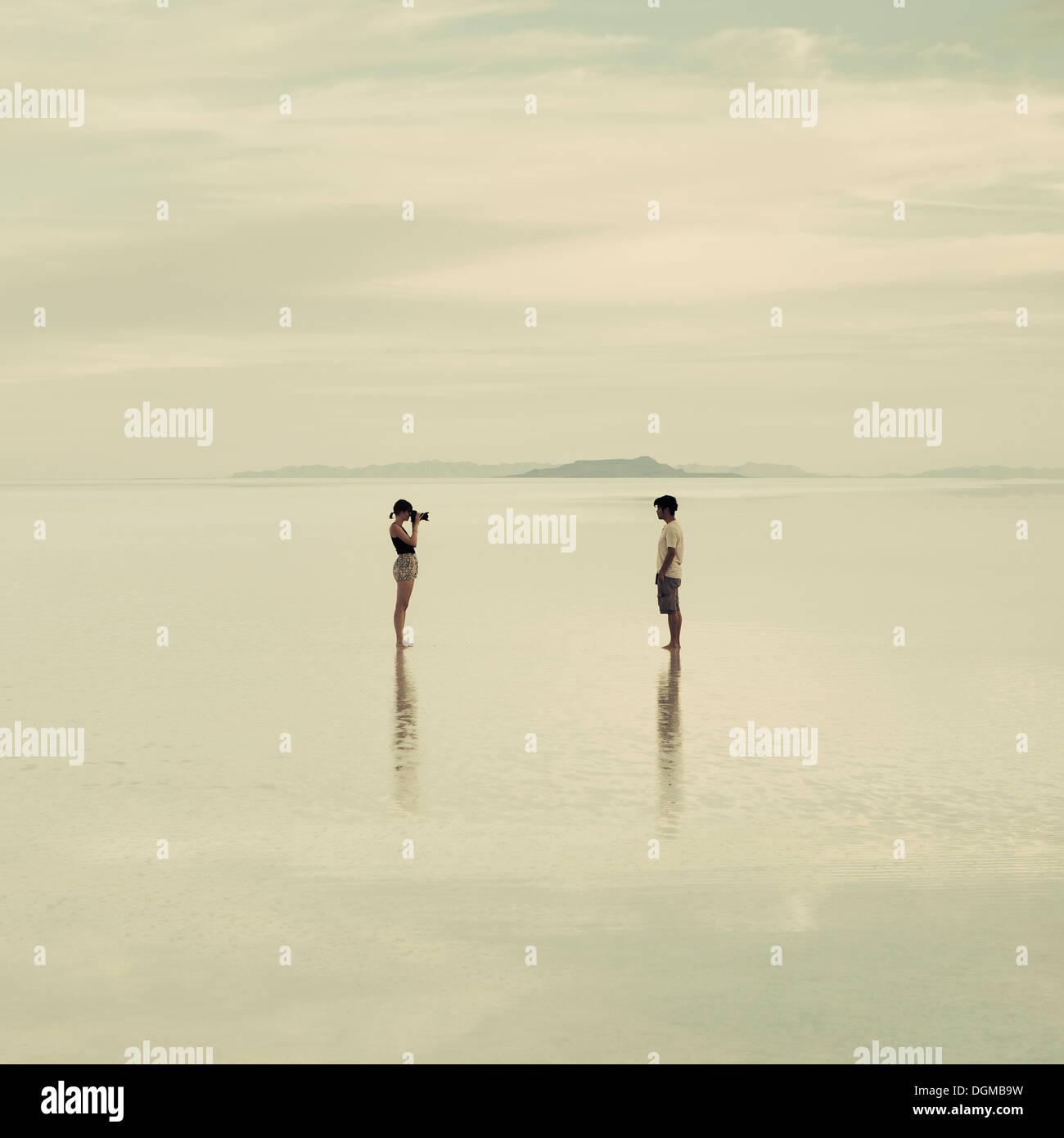 El hombre y la mujer de pie en las salinas de Bonneville, inundada de tomar fotografías de cada uno de los demás al anochecer. Imagen De Stock
