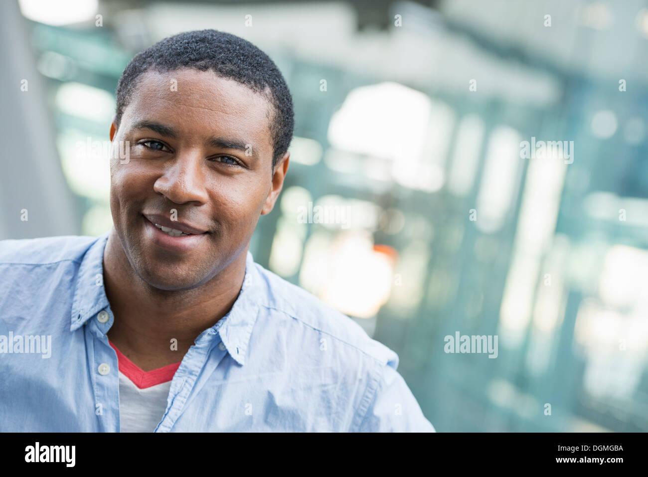 El verano en la ciudad. La gente de negocios de ropa informal. Un hombre hermoso en una camisa azul. Imagen De Stock