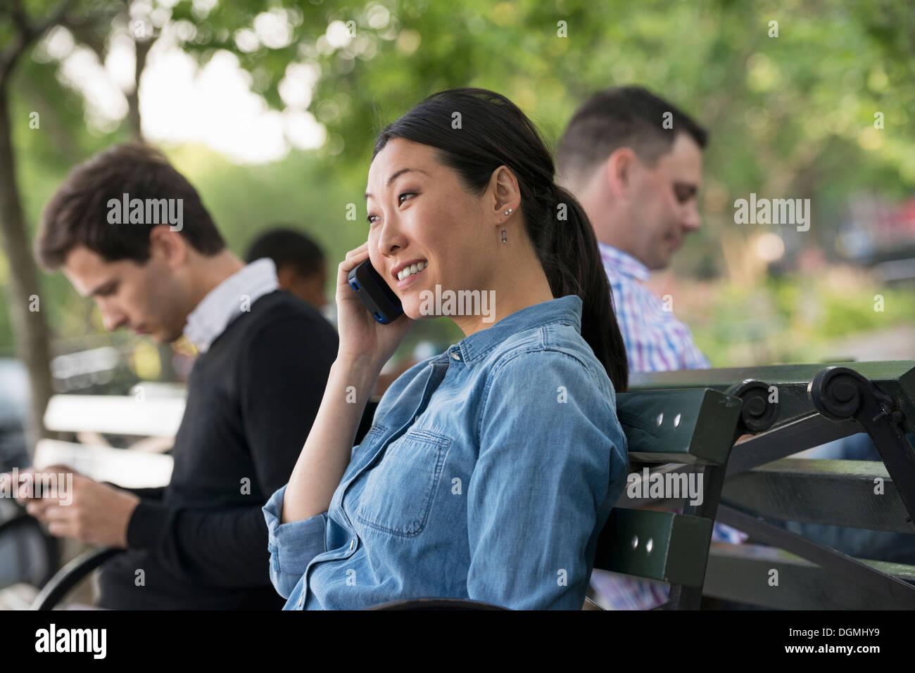 El verano en la ciudad. Una mujer y tres hombres sentados en el parque, cada uno en su propio teléfono o usando un tablet. Imagen De Stock