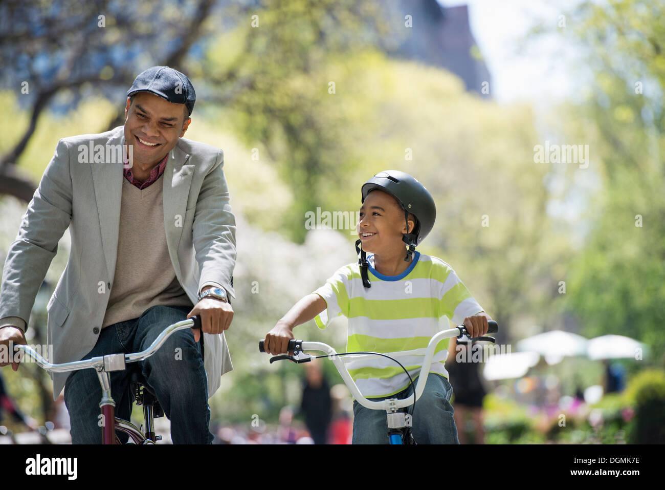 Una familia en el parque en un día soleado. Padre e hijo en bicicleta Imagen De Stock