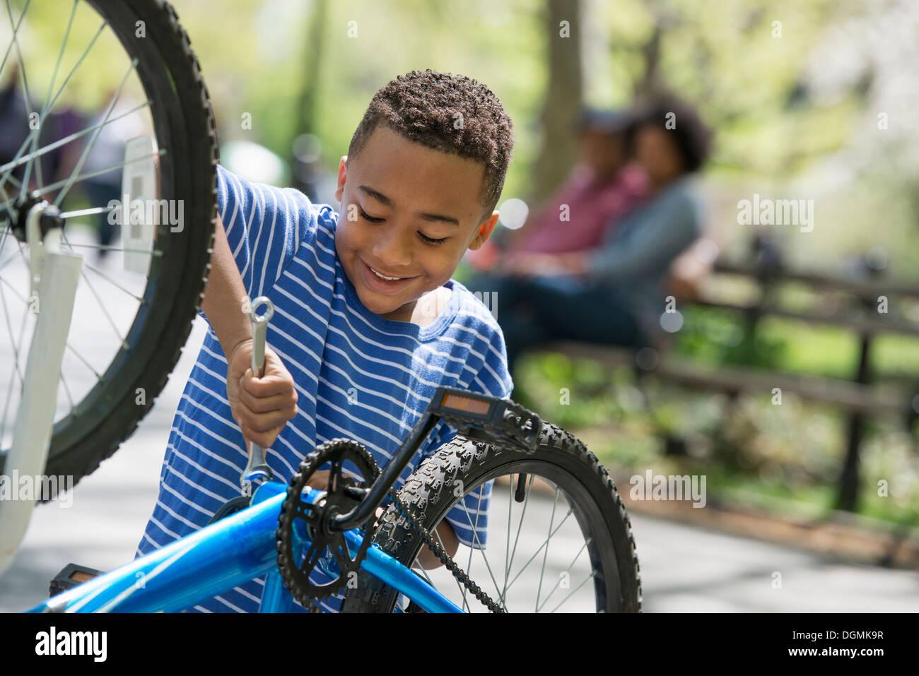 Una familia en el parque en un día soleado. Un padre y un hijo de reparar una bicicleta. Imagen De Stock