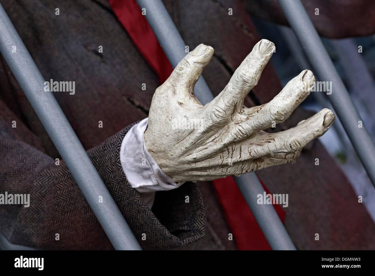 Mano que alcanza a través de los barrotes de la cárcel, casa embrujada figura Imagen De Stock