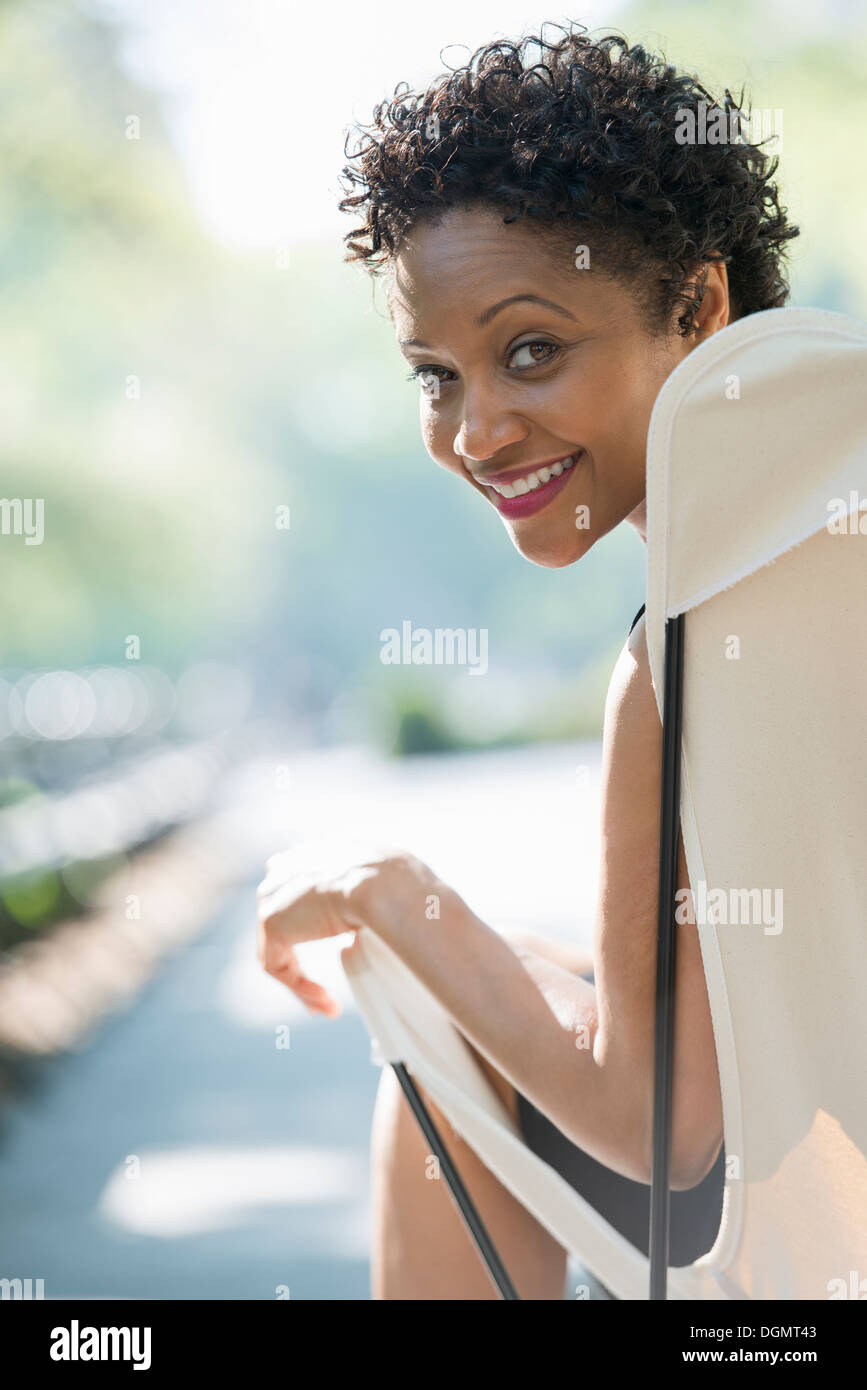 La vida de la ciudad. Una mujer sentada en una silla de camping en un parque mirando por encima del hombro. Imagen De Stock
