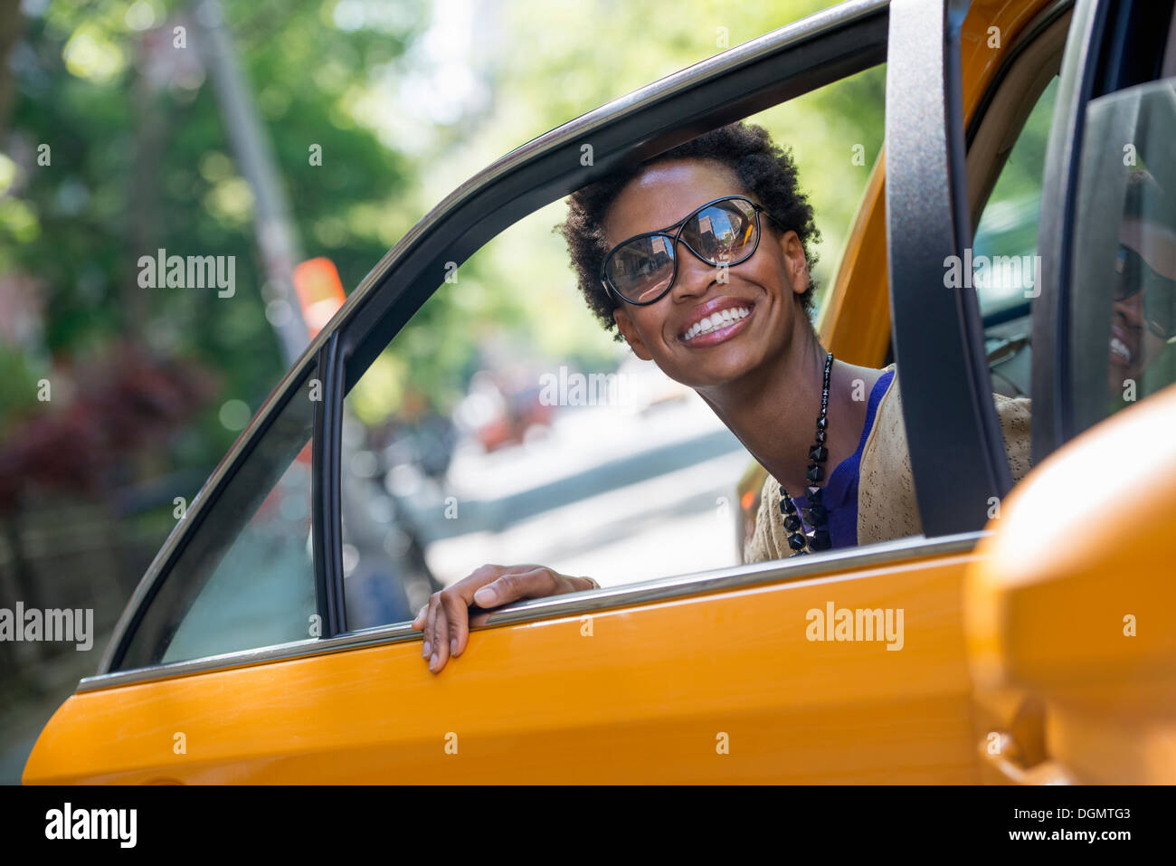 Una mujer saliendo de la parte trasera del asiento del pasajero de un taxi amarillo. Imagen De Stock