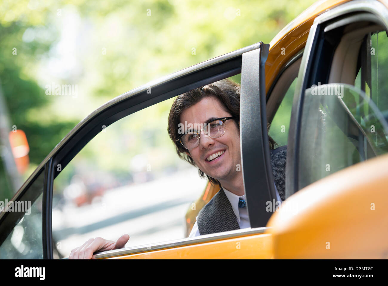 La vida de la ciudad. La gente en movimiento. Un hombre joven en el asiento trasero de un taxi. Imagen De Stock