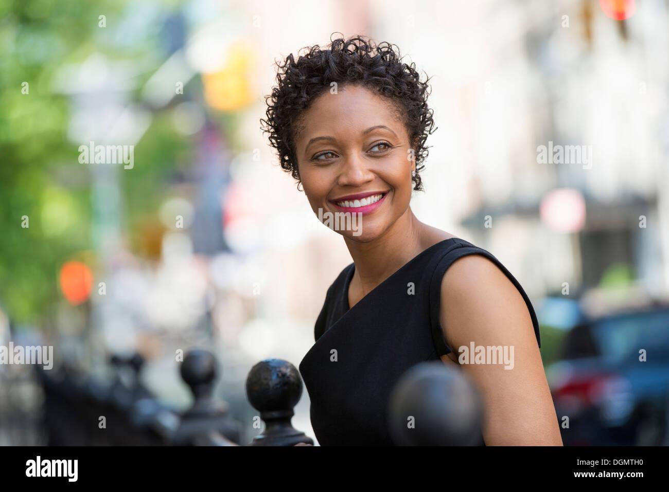 La gente en movimiento. Una mujer en un vestido negro en una calle de la ciudad. Imagen De Stock