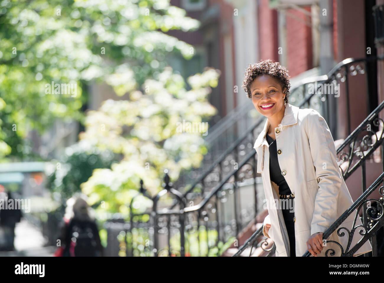 Ciudad. Una mujer caminando por pasos fuera de una casa de ciudad. Foto de stock