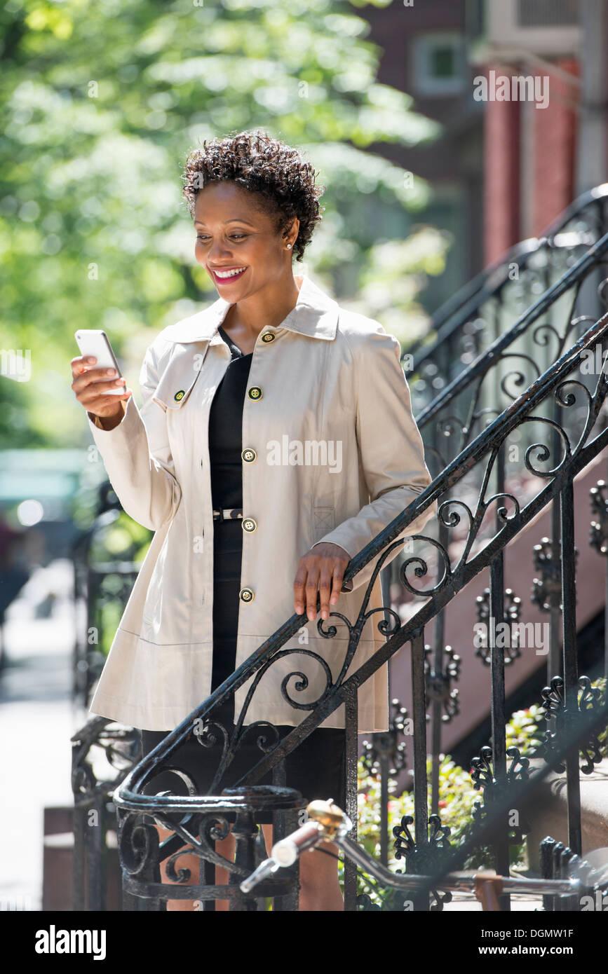 Ciudad. Una mujer en pasos fuera de una casa de ciudad, control de su teléfono inteligente. Foto de stock