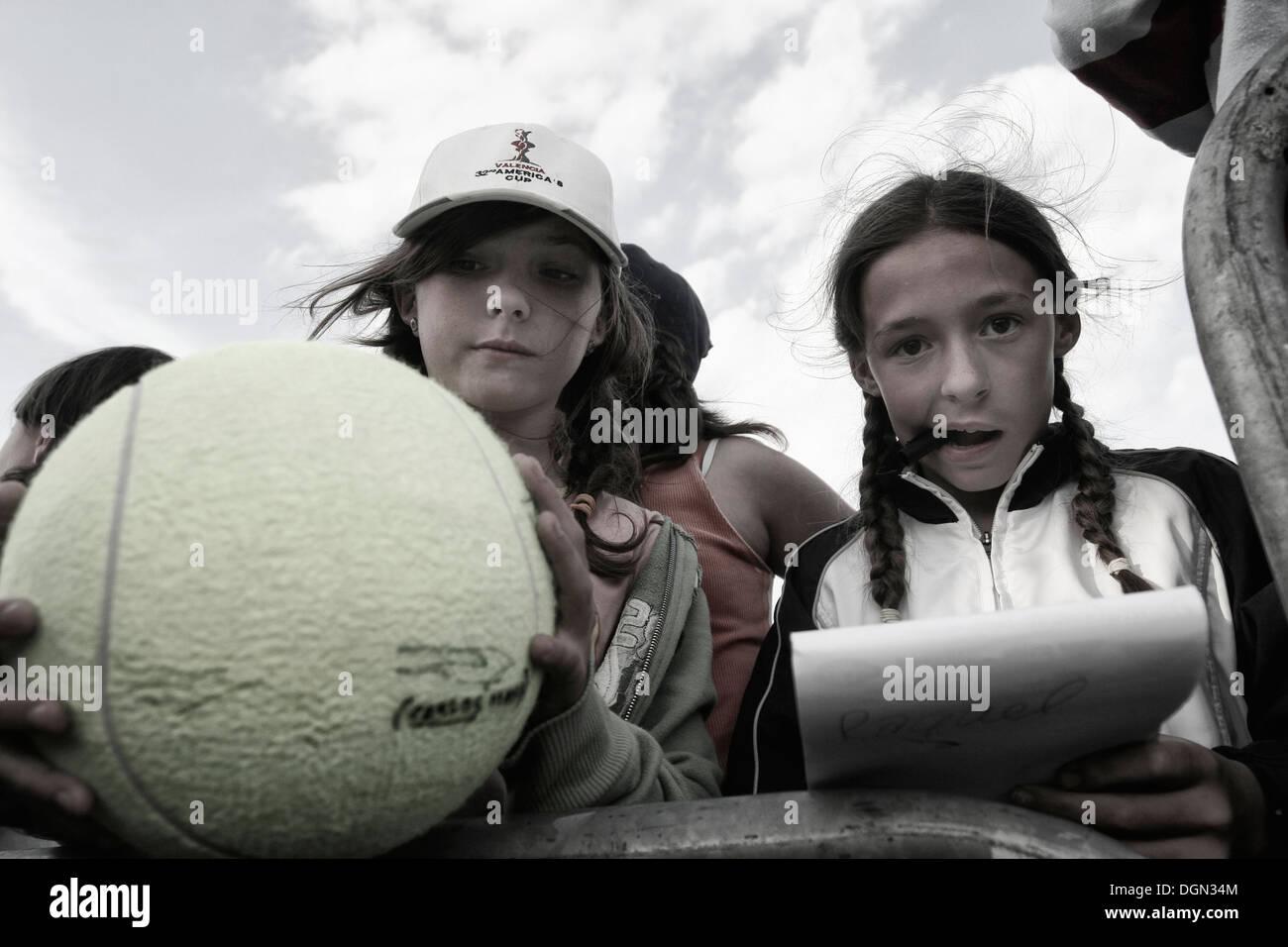 Los jóvenes a los aficionados al tenis esperan a los jugadores en torno a venir a pedir su autógrafo en un torneo local en Mallorca, España Foto de stock