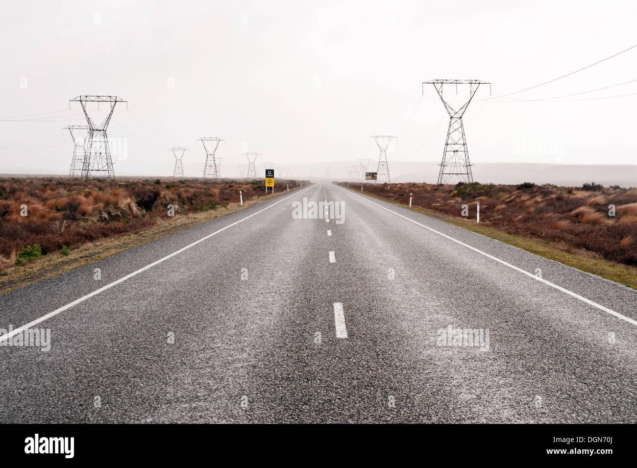 Líneas de energía eléctrica a lo largo de la autopista 1, la carretera del desierto en la región volcánica cerca del Lago Taupo, Isla del Norte, Nueva Zelanda Imagen De Stock
