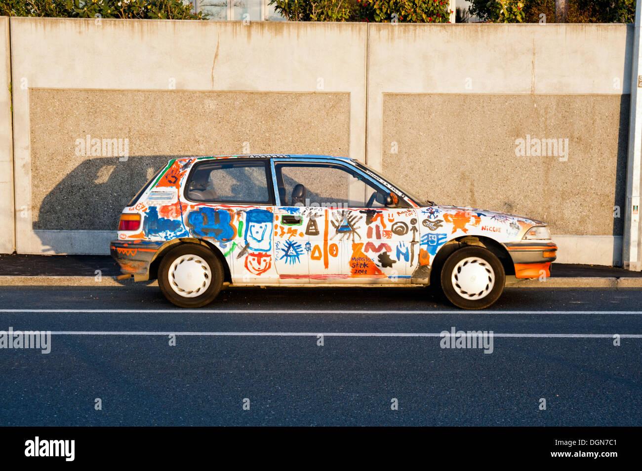 Viejo coche adornado con graffiti, la ciudad de Nelson, Nueva Zelanda. Imagen De Stock