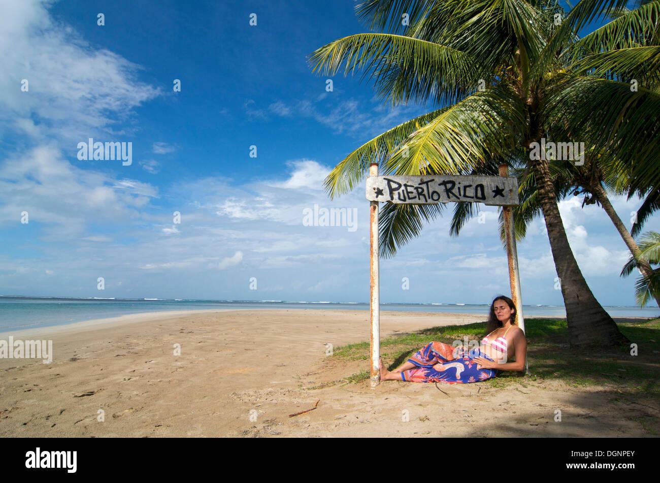 Turista que yacía bajo un cartel con las palabras de Puerto Rico, la playa Luquillo, Puerto Rico, el Caribe Imagen De Stock