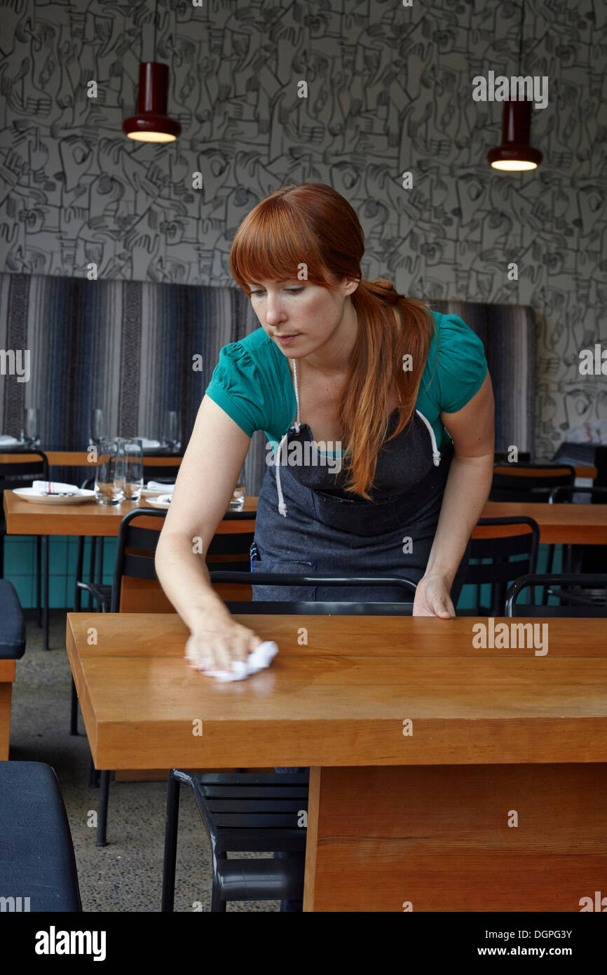 Mujer adulta media tabla de limpieza en restaurante. Foto de stock