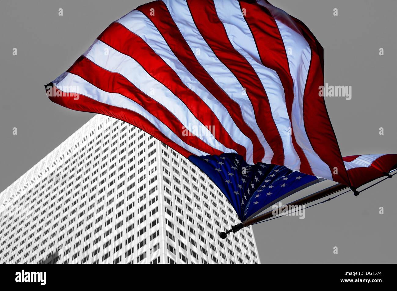 La bandera americana en EE.UU. volando en frente de un rascacielos, New York City, New York, Estados Unidos Foto de stock