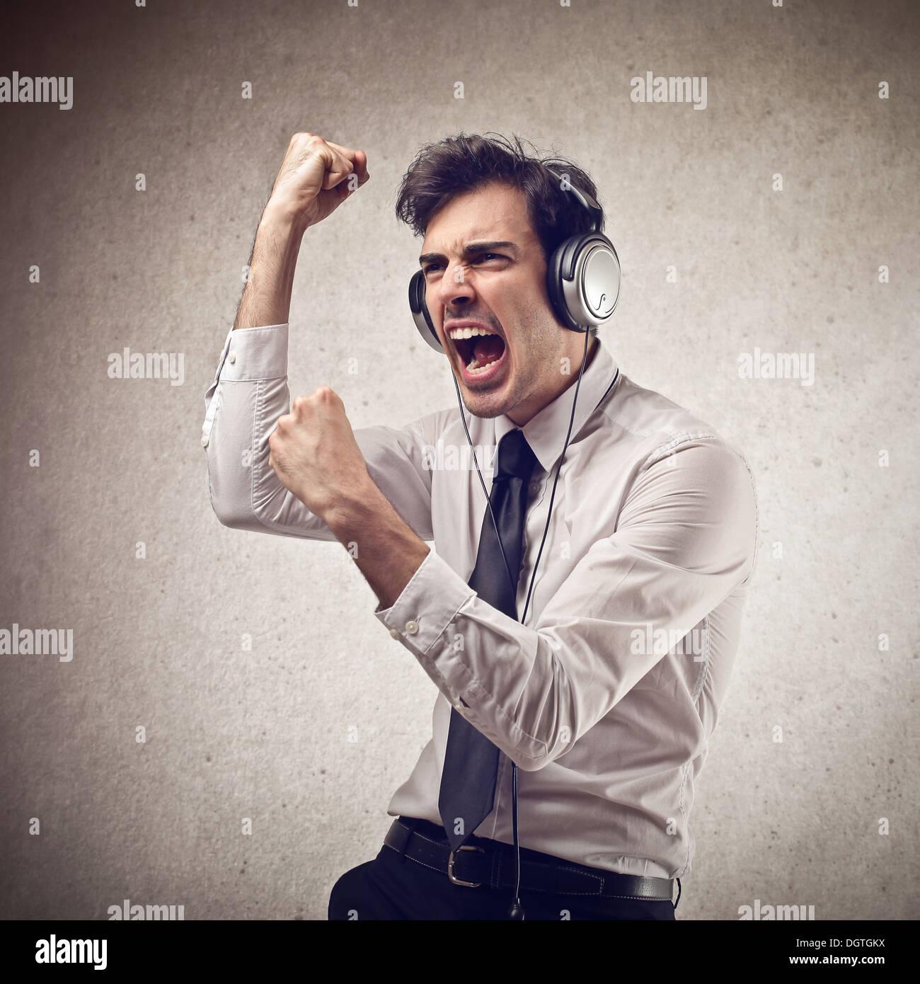 Joven trabajador de oficina bailando mientras se escucha la música con auriculares Imagen De Stock