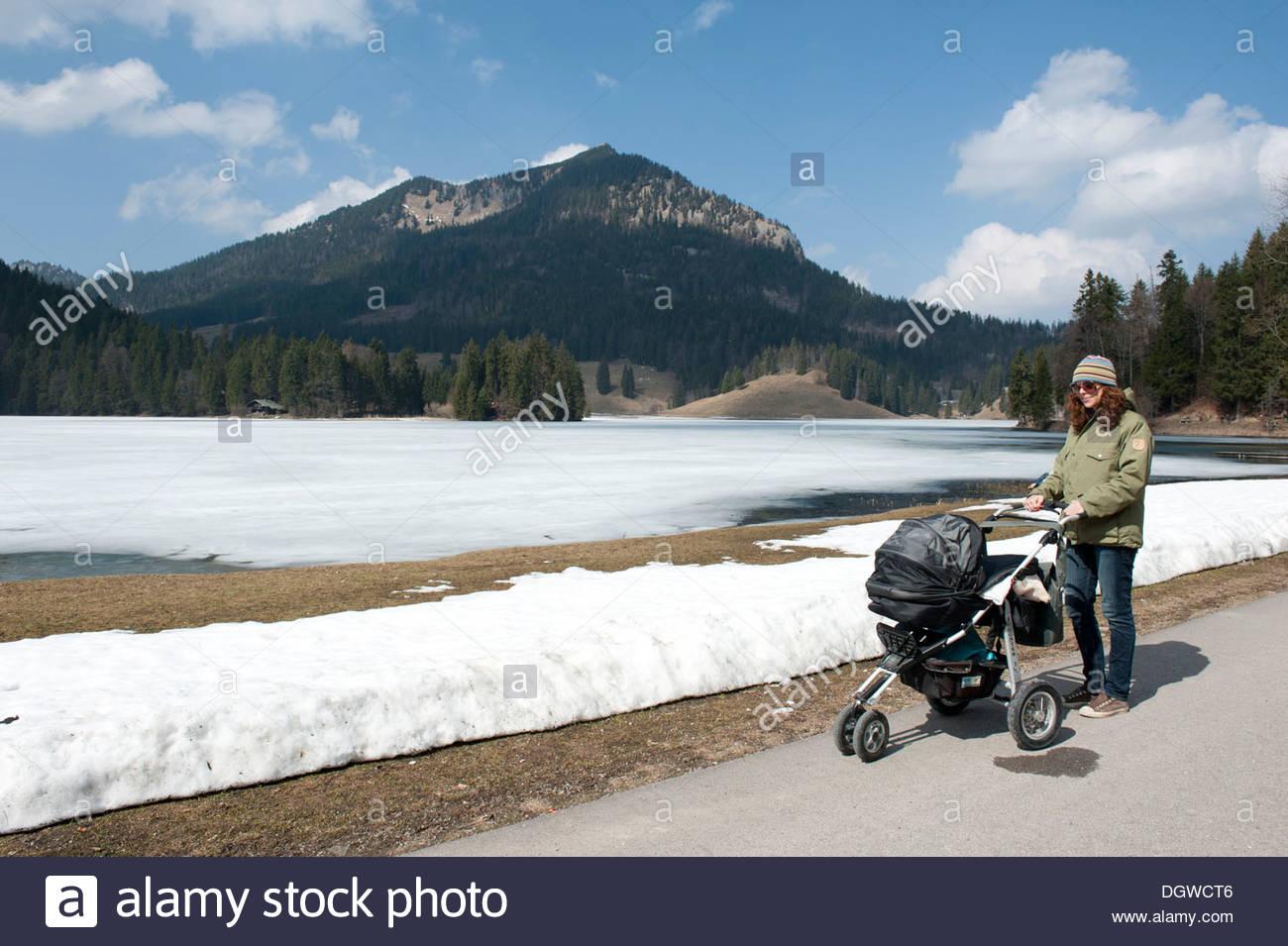 Madre con el carro del bebé caminando sobre todavía congeladas sobre el lago Spitzingsee en primavera, 1084 m, parches de nieve Imagen De Stock