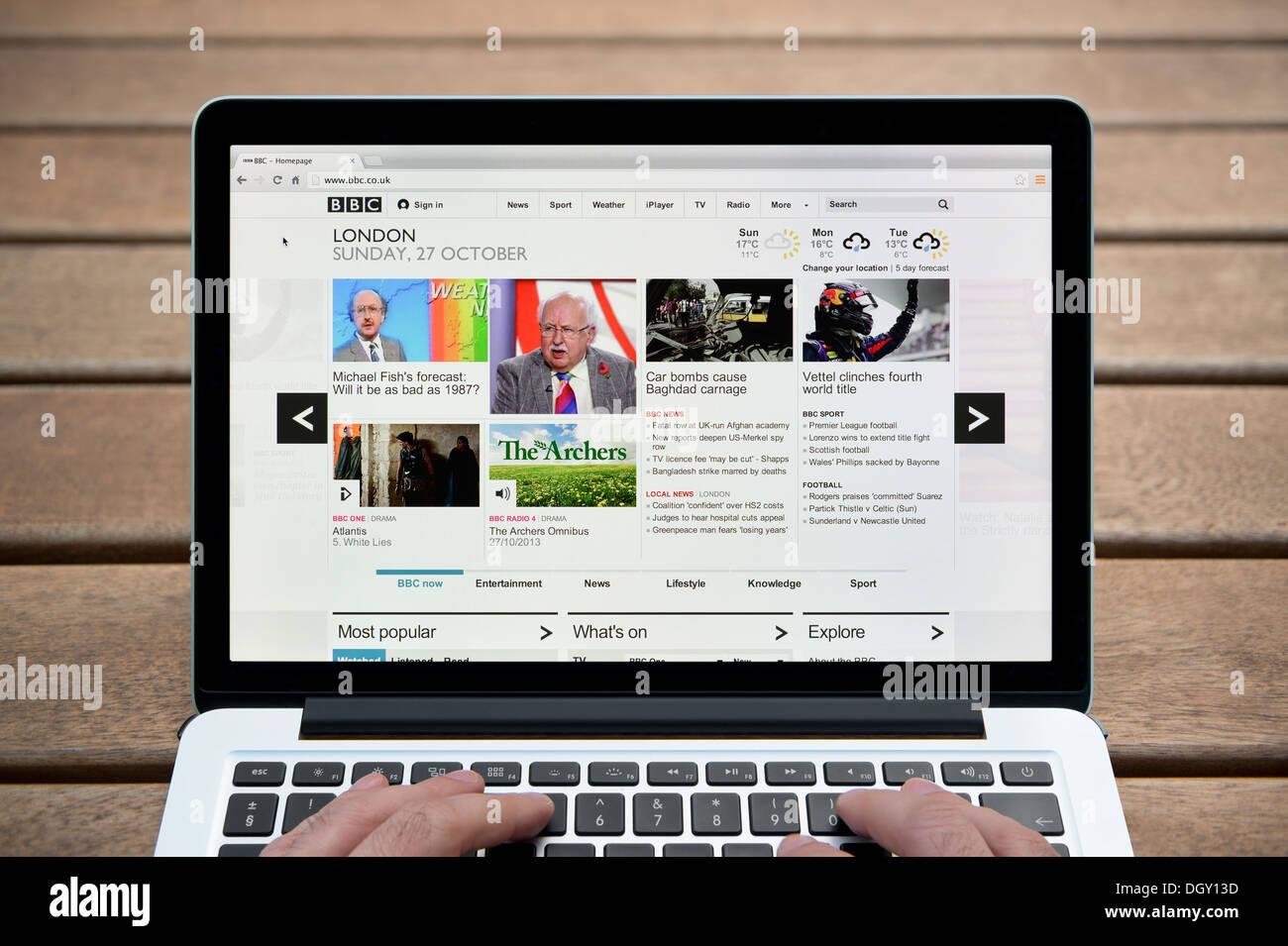 La BBC Online website en un MacBook contra un banco de madera de fondo al aire libre incluyendo un hombre de dedos (uso Editorial solamente). Imagen De Stock
