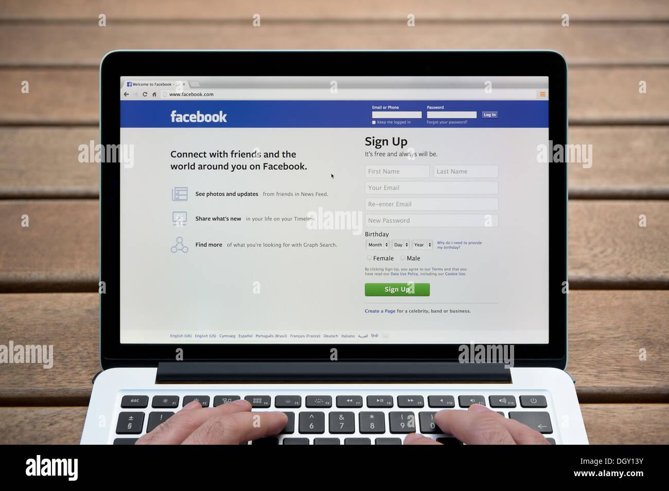 El sitio web de Facebook en un MacBook contra un banco de madera de fondo al aire libre incluyendo un hombre de dedos (uso Editorial solamente). Imagen De Stock
