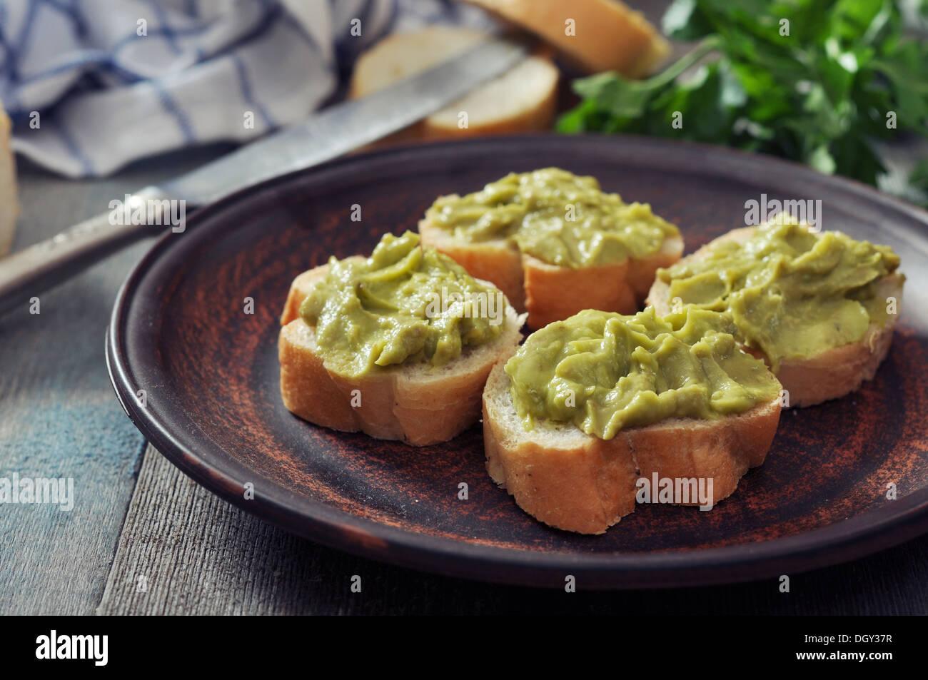 Delicioso aperitivo canapés de pan y guacamole se sirve con perejil closeup Imagen De Stock