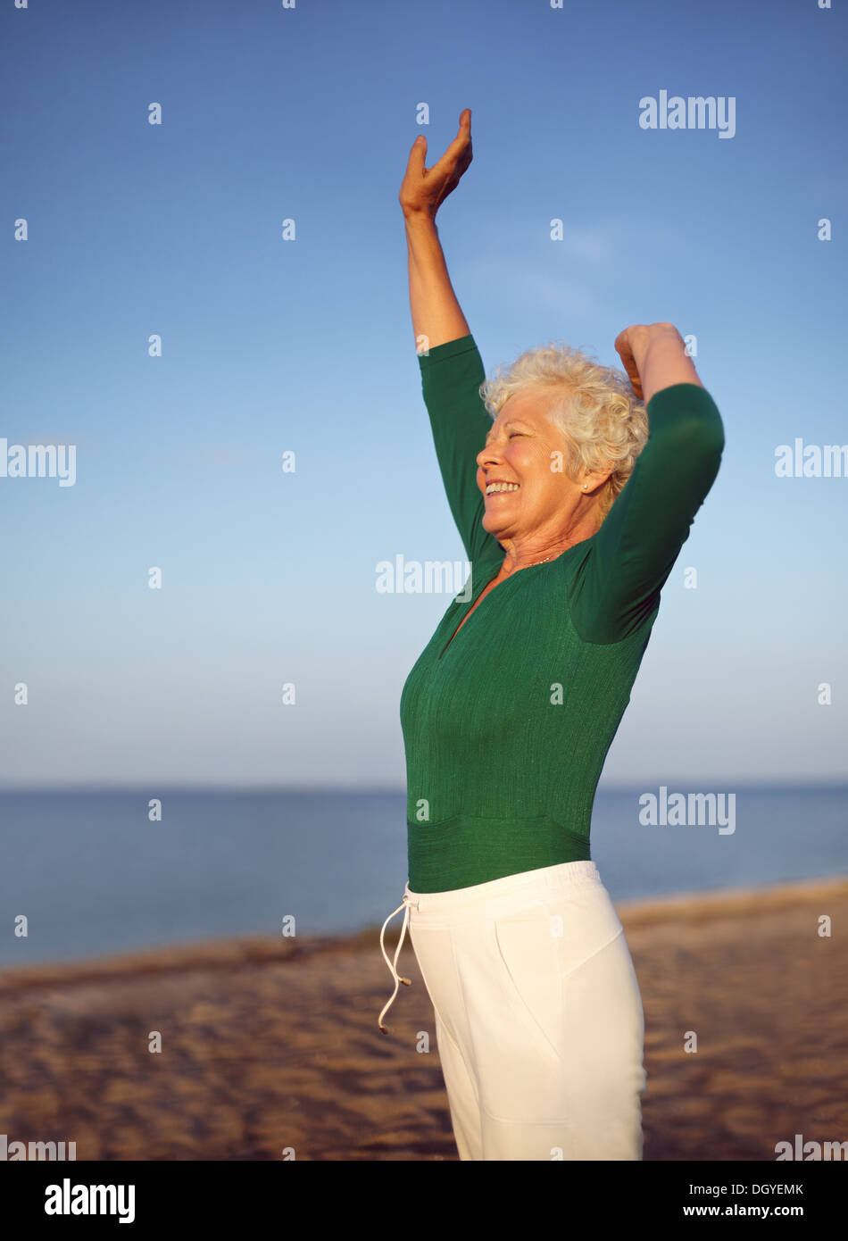 Mujer mayor estiramiento en la arena de la playa. Madura mujer caucásica ejercer por el mar. Imagen De Stock
