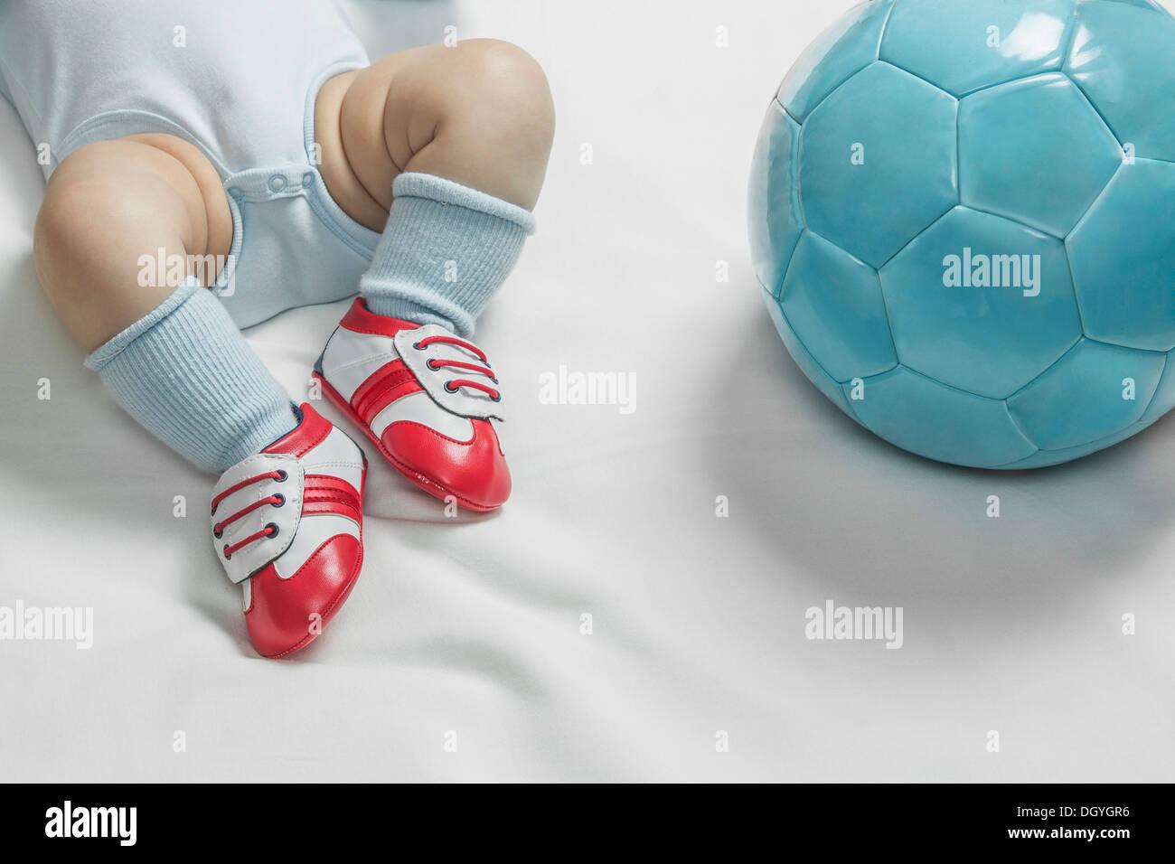 b8bc77c7fb492 Un bebé bebé niño usando zapatos de fútbol tumbado junto a un balón de  fútbol jpg