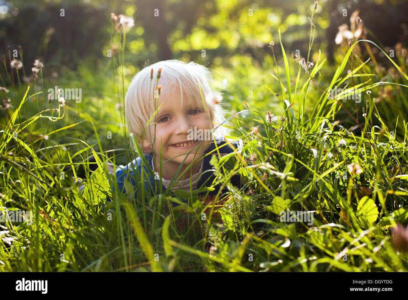 Niñito alegre rubia en la hierba Foto de stock