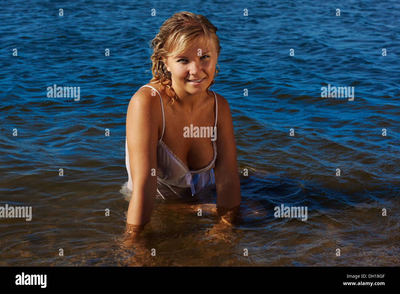 cc731e409 Hermosa chica rubia posando en peignoir húmedo en las aguas de mar ...