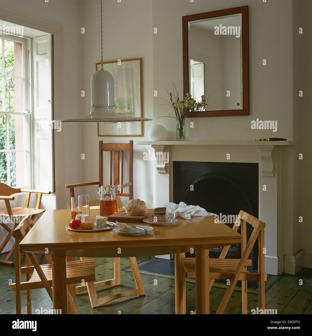 Luz colgante encima de sillas de madera plegables un simple juego de ...