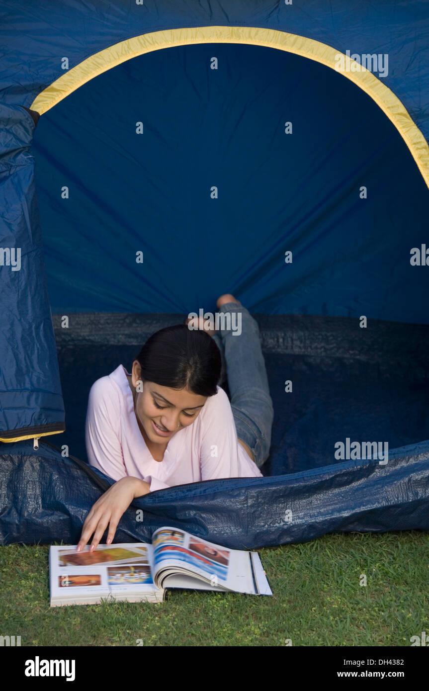 Mujer acostado en una tienda de campaña y leyendo una revista Foto de stock