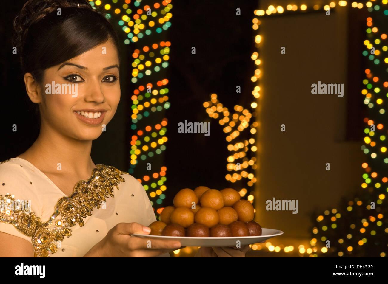 Mujer sosteniendo dulces en una placa y sonriente Foto de stock