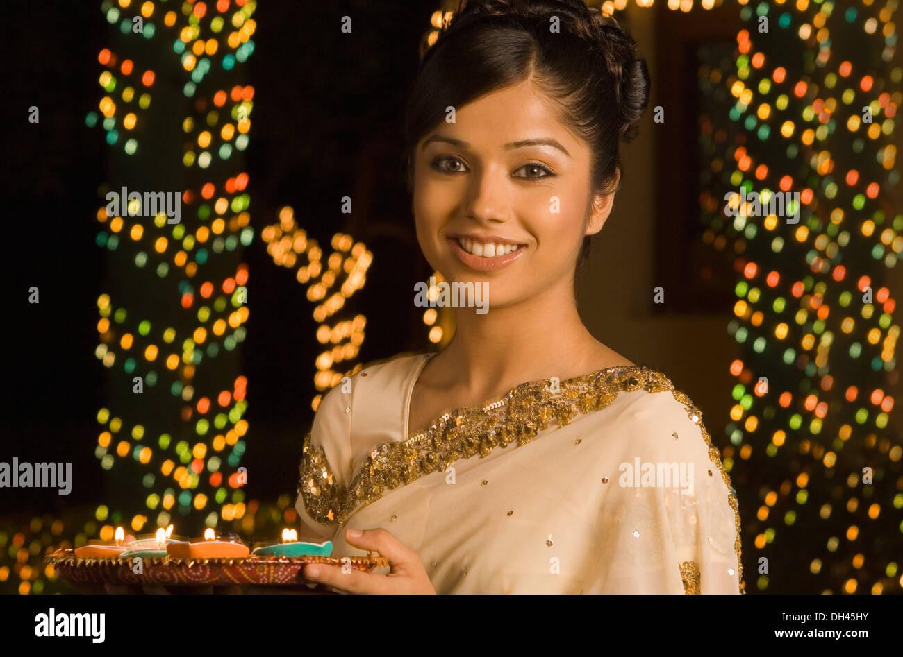 Mujer sosteniendo ofrenda religiosa y sonriente Foto de stock