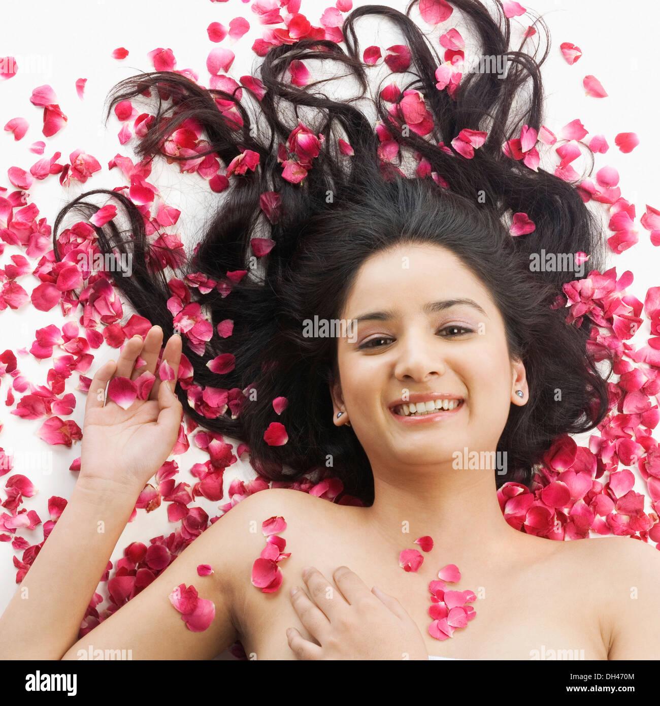 Mujer acostada sobre pétalos de rosas Foto de stock