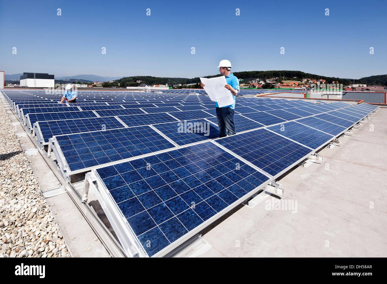 Dos técnicos inspeccionar una planta de energía solar, Wollsdorf, distrito de Weiz, Estiria, Austria Imagen De Stock