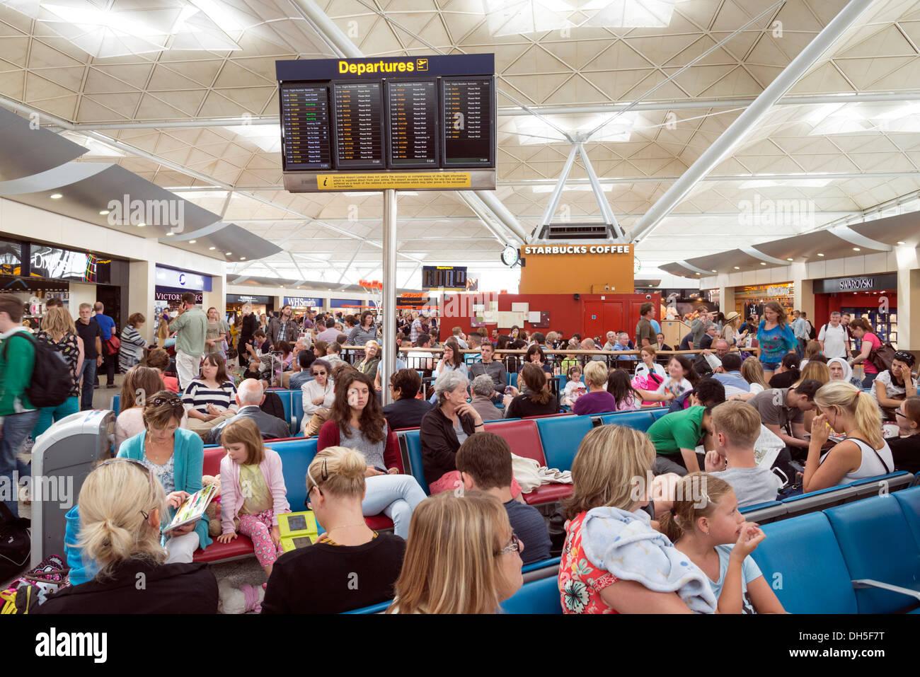 Gente esperando en la atestada sala de salidas del aeropuerto de Stansted, Inglaterra, Reino Unido. Imagen De Stock
