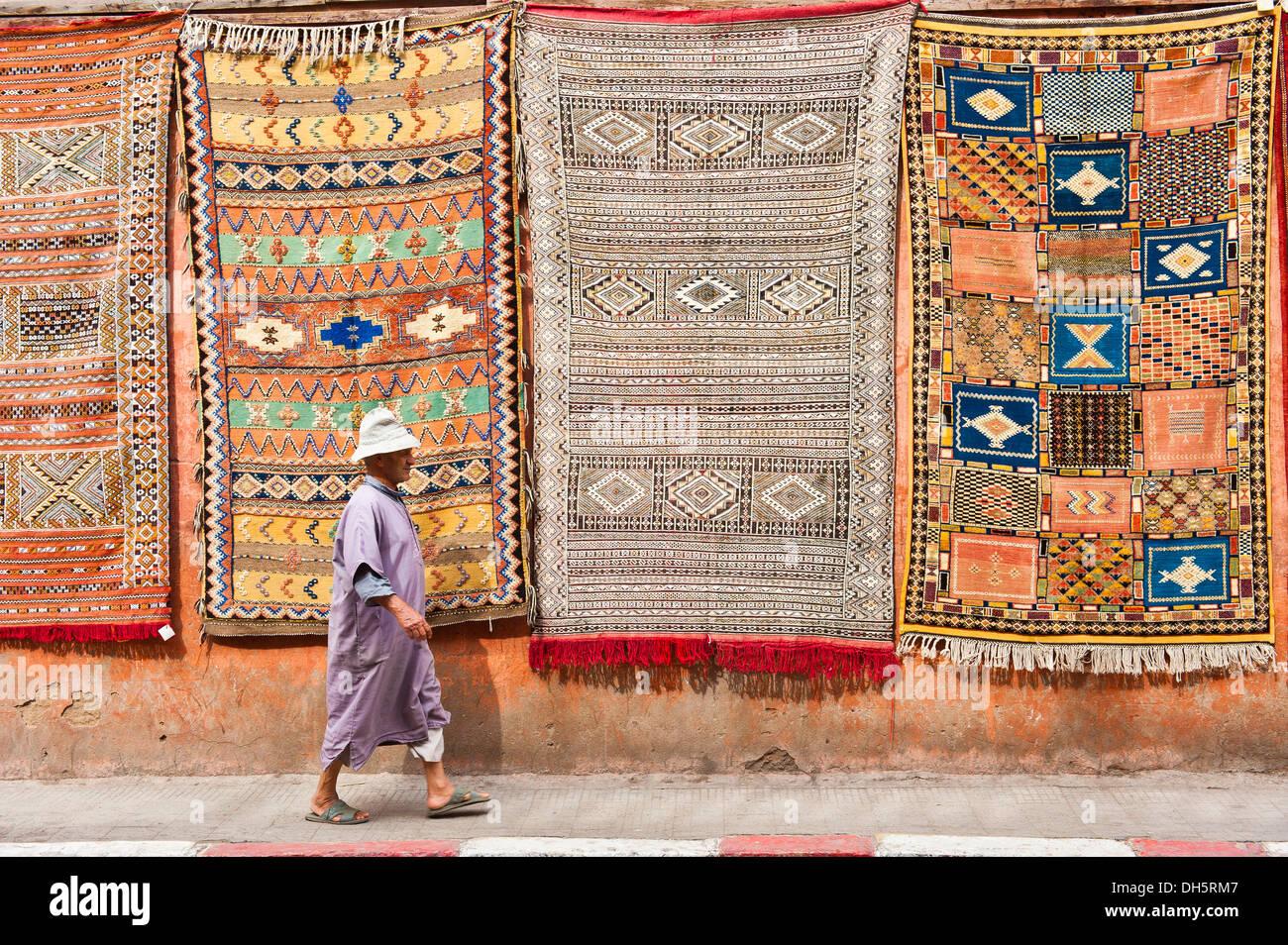 Las alfombras o tapetes con símbolos árabes y bereberes y patrones, colgando de una fachada para la venta, un anciano paseando djellabah Imagen De Stock