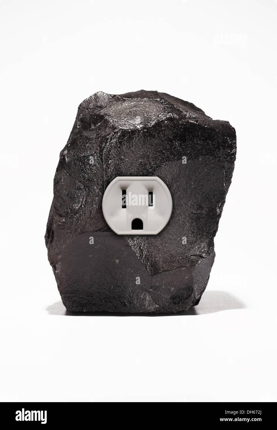 Un gran trozo de carbón negro con una sola toma de corriente eléctrica. Fondo blanco Imagen De Stock