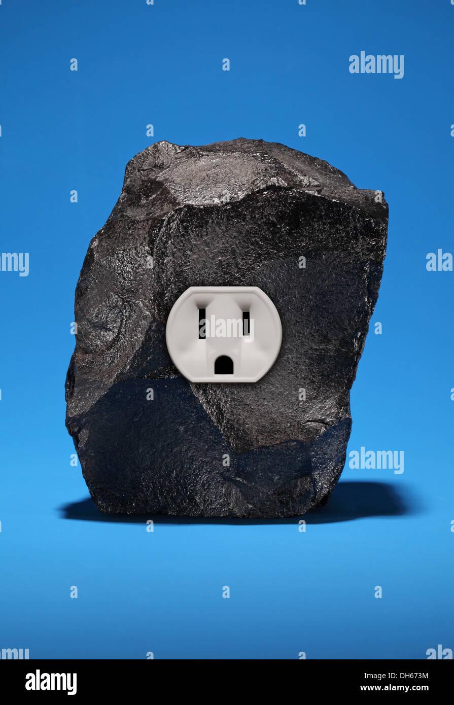 Un gran trozo de carbón negro con una sola toma de corriente eléctrica. Fondo azul brillante Imagen De Stock