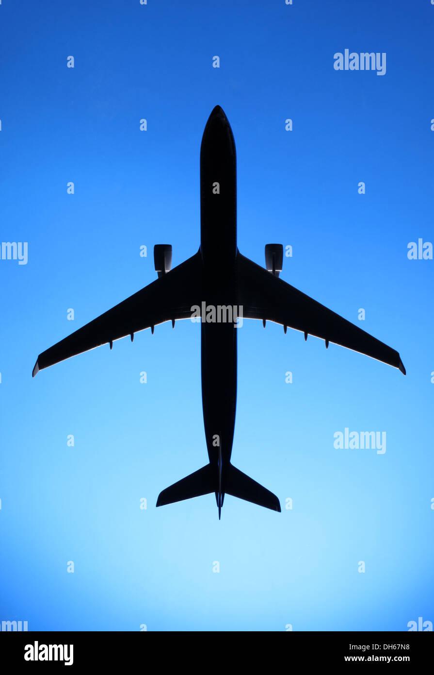 Un modelo plástico de un avión comercial avión volando en el cielo azul Imagen De Stock