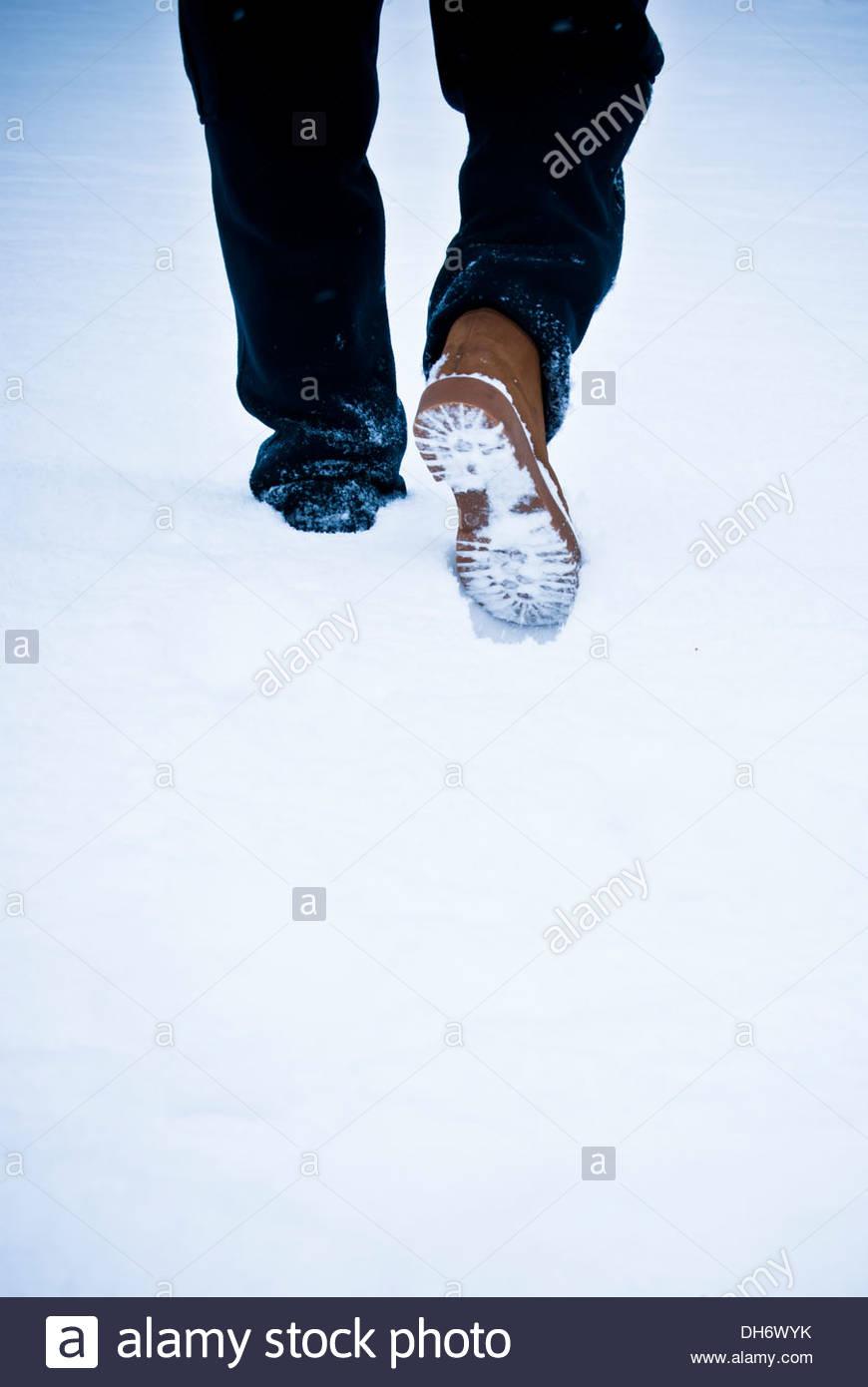 Las piernas de un hombre caminando en la nieve. Imagen De Stock