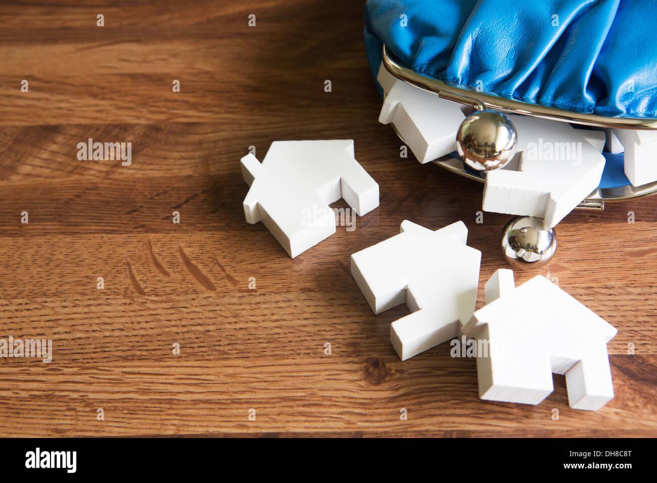 Bolso con modelos de casas sobre superficie de madera Imagen De Stock