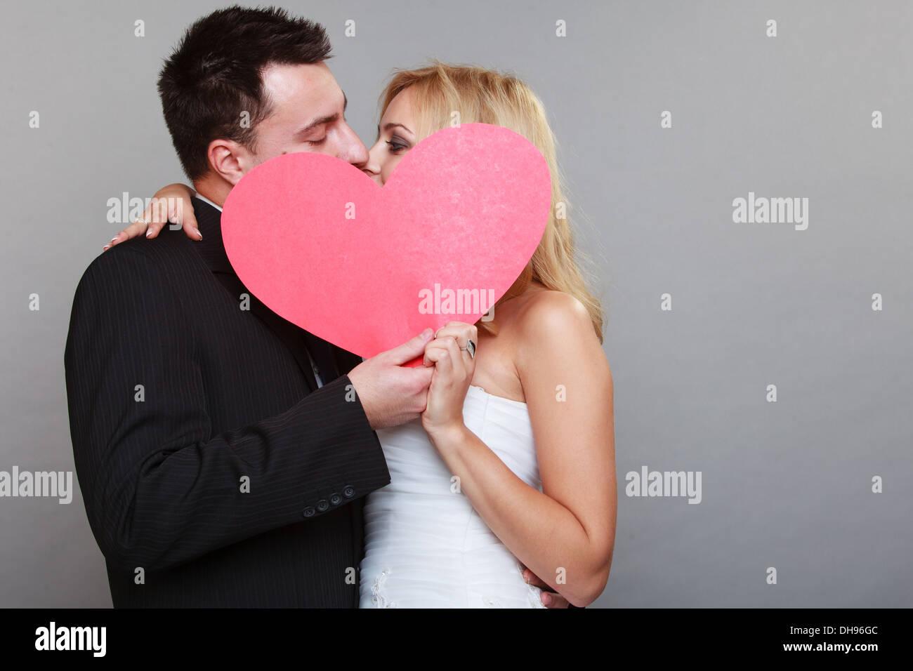 Día de la boda. Feliz para el novio y la novia rubia besar detrás de ...