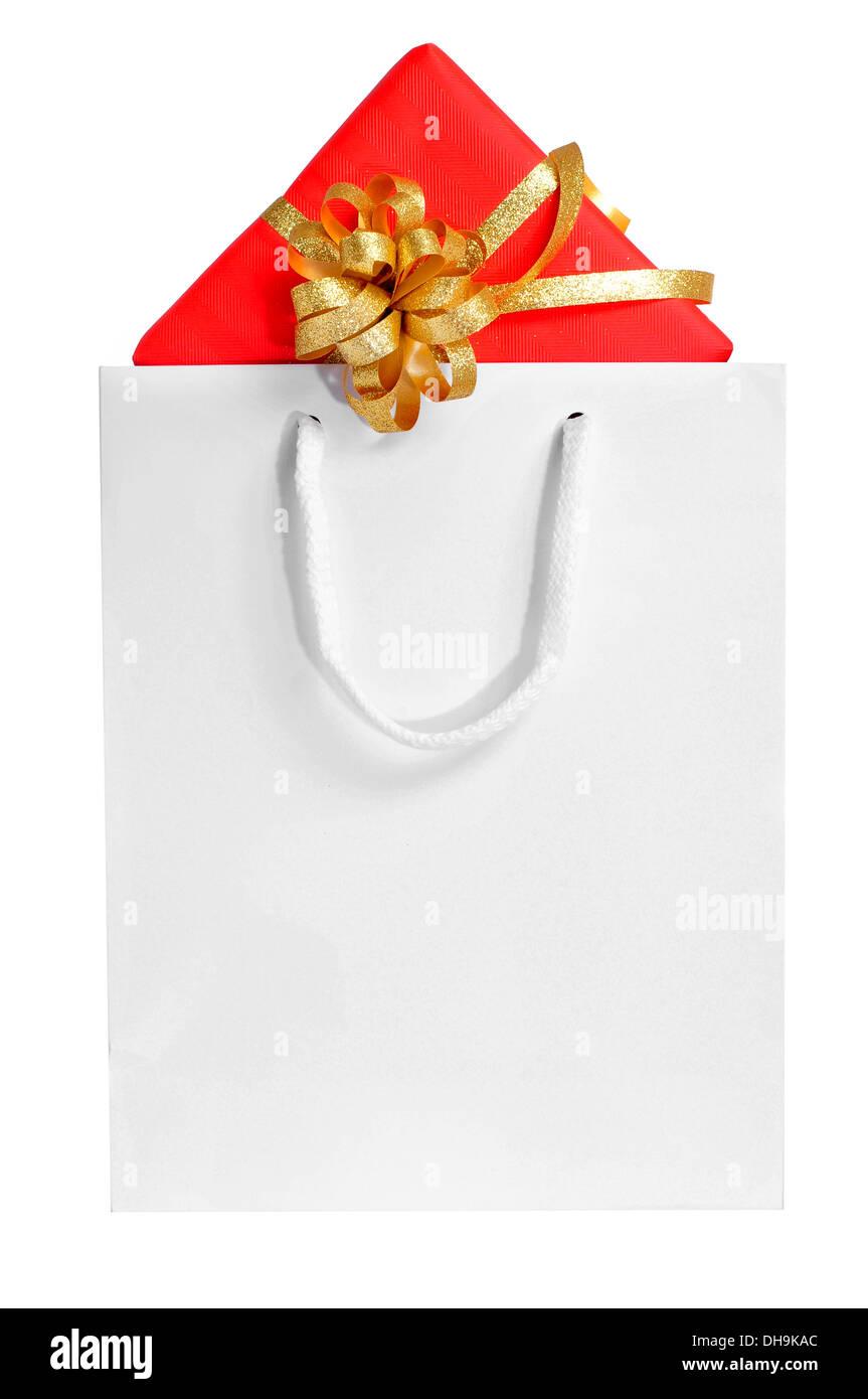 Un regalo envuelto con papel de regalo rojo y con una cinta dorada, en una bolsa de compras sobre un fondo blanco. Imagen De Stock