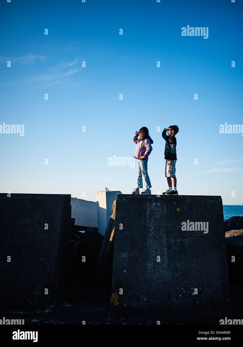 Niño y niña de pie en la pared del puerto y miran al mar. Foto de stock