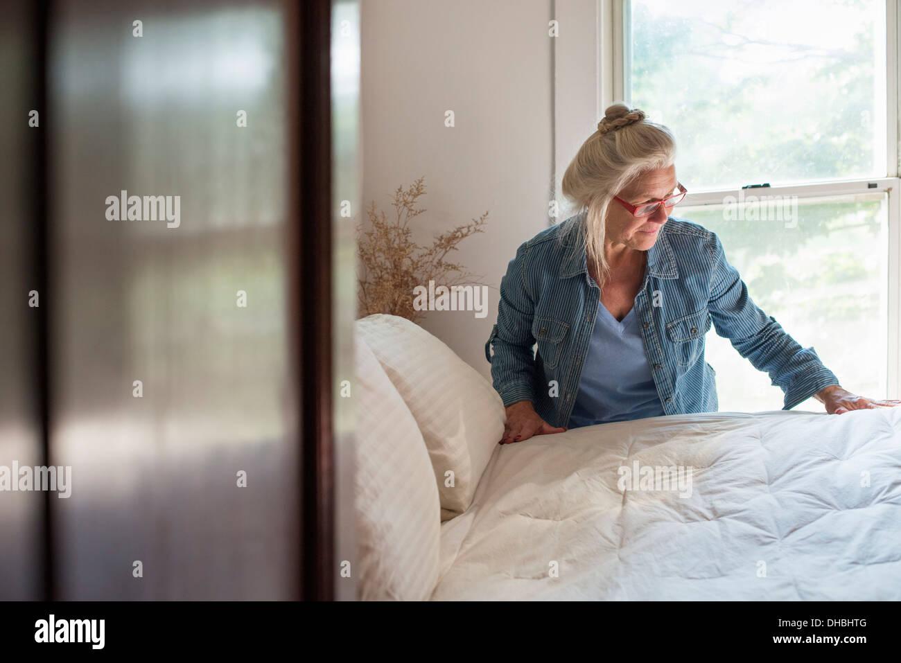 Una granja en el país, una mujer haciendo una cama en un dormitorio. Imagen De Stock