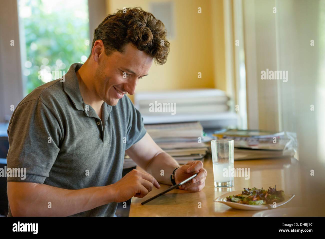 Una persona sentada sola en un café. Un hombre usando una tableta digital. Imagen De Stock